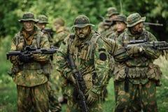 Grupo de forças especiais dos soldados durante a invasão na floresta Fotografia de Stock
