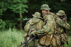 Grupo de forças especiais dos soldados durante a invasão na floresta Fotografia de Stock Royalty Free