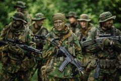 Grupo de forças especiais dos soldados durante a invasão na floresta Foto de Stock