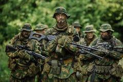 Grupo de forças especiais dos soldados durante a invasão na floresta Foto de Stock Royalty Free