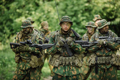 Grupo de forças especiais dos soldados durante a invasão na floresta Imagens de Stock