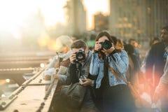 Grupo de fotógrafos de los turistas en el puente de Brooklyn durante el Su Fotos de archivo libres de regalías