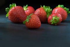Grupo de fresas frescas que mienten en una tabla de piedra oscura Fotos de archivo