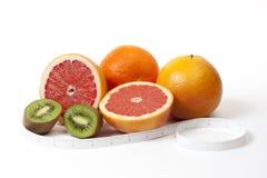 Grupo de frutas tropicales y cinta métrica en pulgadas sobre blanco Imagen de archivo