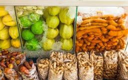 Grupo de frutos frescos e de conserva (manga, goiaba, tamarindo, feijão, 'batata doce') na caixa de armazenamento frio no mercado Fotografia de Stock