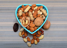 Grupo de frutos secos em uma bacia & ao redor na tabela Imagens de Stock