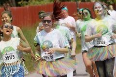 Grupo de funcionamiento, muchachas felices, sonrientes cubiertas con la cuesta colorida Imagen de archivo