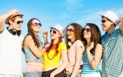 Grupo de gafas de sol que llevan y de sombrero de la gente joven Fotografía de archivo libre de regalías
