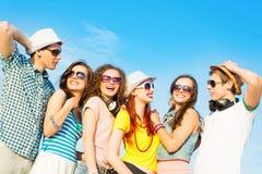Grupo de gafas de sol que llevan y de sombrero de la gente joven Imágenes de archivo libres de regalías