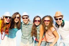 Grupo de gafas de sol que llevan y de sombrero de la gente joven Foto de archivo