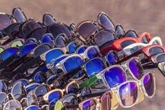 Grupo de gafas de sol expuestas en un mercado imagen de archivo