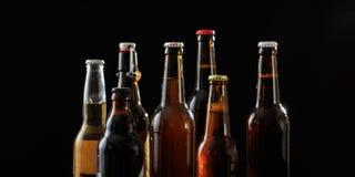 Grupo de garrafas de cerveja no fundo preto fotos de stock