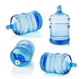 Grupo de garrafas grandes da água no fundo branco Fotos de Stock