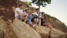 Grupo de gente alegre joven que se sienta en las rocas por la costa y que toca la guitarra, canciones del canto y baile almacen de video