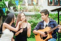 Grupo de gente asiática joven feliz mientras que disfruta a casa del partido y Imágenes de archivo libres de regalías