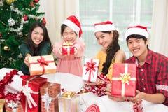 Grupo de gente asiática joven que le lleva a cabo y que da a caja de regalo w Imagen de archivo