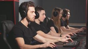 Grupo de gente concentrada en auriculares que disfruta del videojuego en l?nea en los ordenadores del centro del juego almacen de metraje de vídeo