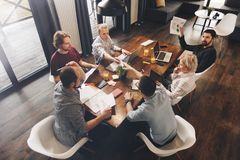 Grupo de gente coworking que se sienta alrededor de la tabla y del workin de madera fotografía de archivo