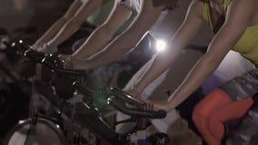 Grupo de gente del deporte en el club de fitness que ejercita en las bicis inmóviles almacen de metraje de vídeo