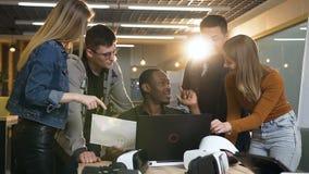 Grupo de gente del inconformista que trabaja con el diagrama usando el ordenador portátil en la oficina moderna almacen de video