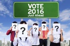 Grupo de gente desconocida y de tablero de votación Foto de archivo libre de regalías