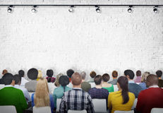 Grupo de gente diversa que hace frente a la pared de ladrillo blanca Fotografía de archivo