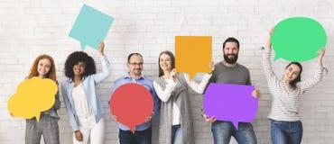 Grupo de gente diversa que lleva a cabo burbujas coloridas del discurso fotografía de archivo libre de regalías
