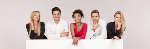 Grupo de gente elegante con el tablero blanco vacío imagen de archivo libre de regalías