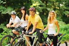 Grupo de gente feliz atractiva en las bicicletas en el campo Imagen de archivo