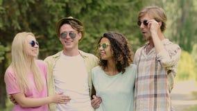 Grupo de gente feliz joven que abraza, riendo, teniendo buen tiempo al aire libre en parque almacen de video