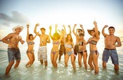 Grupo de gente feliz que baila en la playa Imagen de archivo