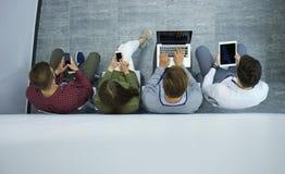 Grupo de gente joven atractiva que se sienta en el piso usando un ordenador portátil, Tablet PC, teléfonos elegantes, sonriendo Imagen de archivo libre de regalías