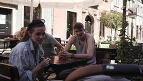 Grupo de gente joven con los niños que almuerzan en un café en la calle almacen de metraje de vídeo