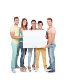 Grupo de gente joven con un cartel en blanco Fotos de archivo libres de regalías