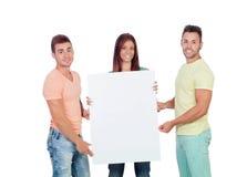 Grupo de gente joven con un cartel en blanco Imagen de archivo libre de regalías