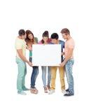 Grupo de gente joven con un cartel en blanco Foto de archivo libre de regalías