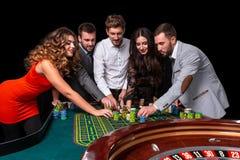 Grupo de gente joven detrás de la tabla de la ruleta en un casino fotografía de archivo libre de regalías