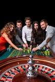 Grupo de gente joven detrás de la tabla de la ruleta en un casino foto de archivo libre de regalías