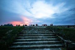 Grupo de gente joven durante la socialización de la puesta del sol imagen de archivo