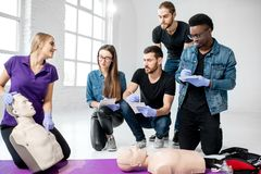 Grupo de gente joven durante los cursos médicos de los primeros auxilios dentro fotografía de archivo