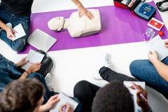 Grupo de gente joven durante los cursos médicos de los primeros auxilios dentro imágenes de archivo libres de regalías