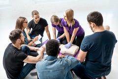 Grupo de gente joven durante los cursos médicos de los primeros auxilios dentro fotografía de archivo libre de regalías