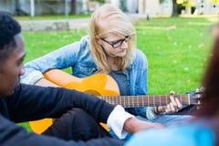 Grupo de gente joven en el parque que hace música Foto de archivo libre de regalías