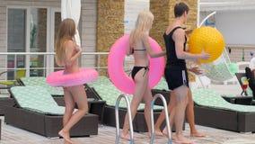 Grupo de gente joven en trajes de baño con el anillo inflable el día de fiesta en verano metrajes