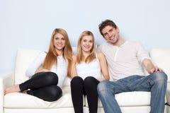 Grupo de gente joven en un sofá Fotos de archivo libres de regalías