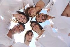 Grupo de gente joven feliz en círculo en la playa Fotografía de archivo libre de regalías