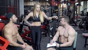 Grupo de gente joven de los deportes que discute un plan de entrenamiento en el gimnasio metrajes
