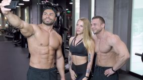 Grupo de gente joven de los deportes que toma selfies en el gimnasio metrajes