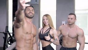 Grupo de gente joven de los deportes que toma selfies en el gimnasio almacen de video