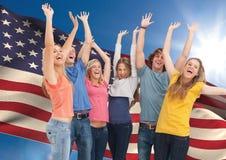 Grupo de gente joven que anima contra bandera americana Imagenes de archivo